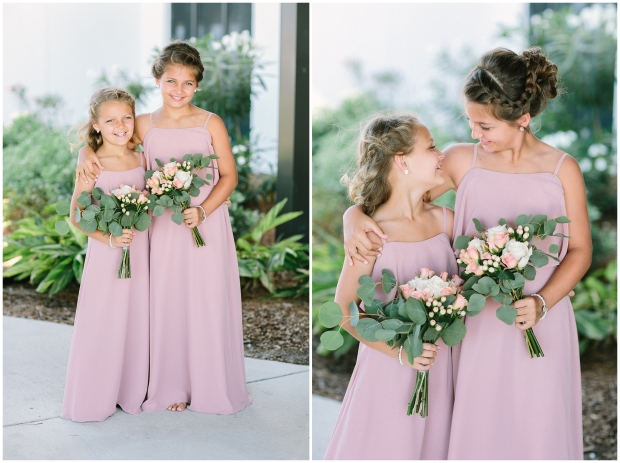 two junior bridesmaids in mauve dresses smiling at each other