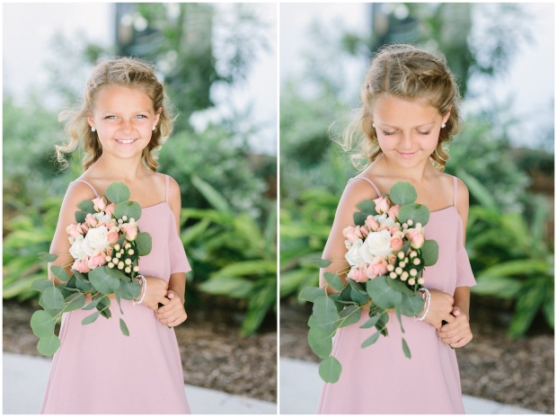 flower girl smiling with small bouquet in pink dress