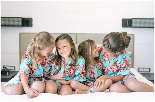 four flower girls sitting together in matching floral robes
