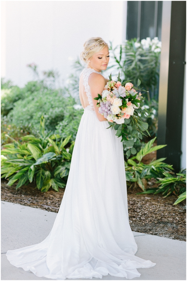 blonde bride looking at colorful bouquet