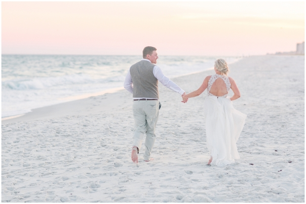 bride and groom running on beach beside of the ocean
