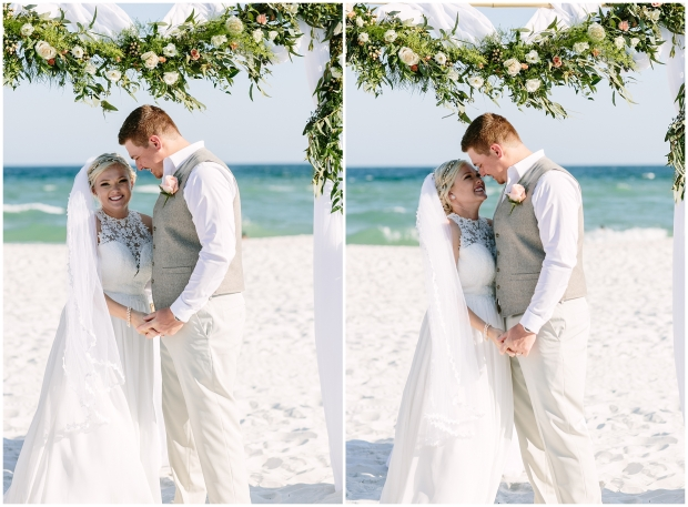 bride and groom on the beach getting married under a floral arbor