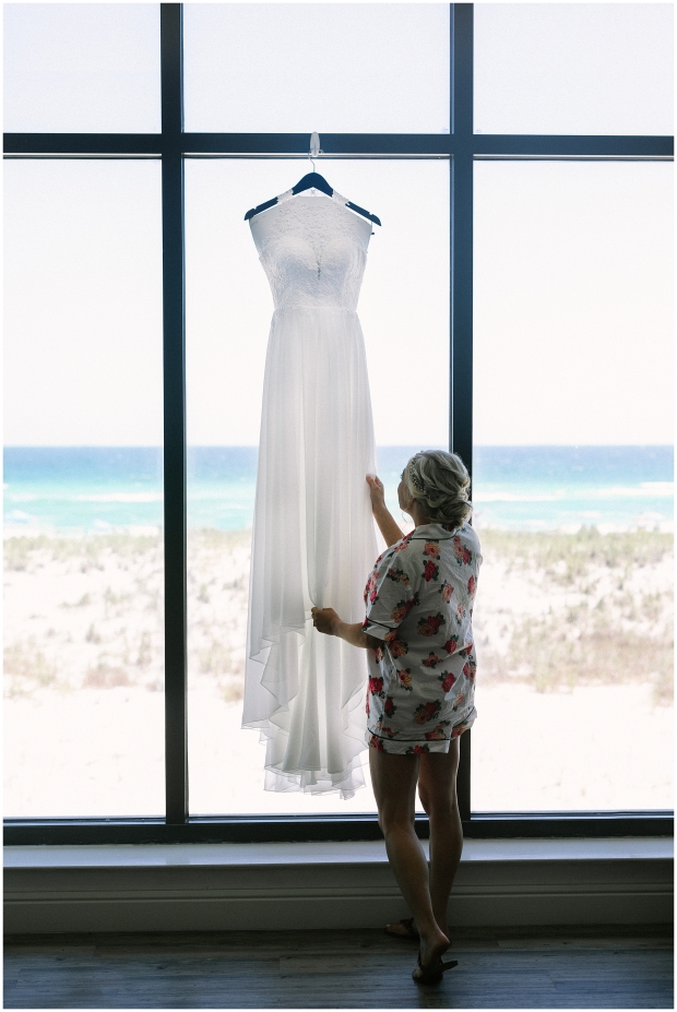 bride in beach front hotel room admiring gown