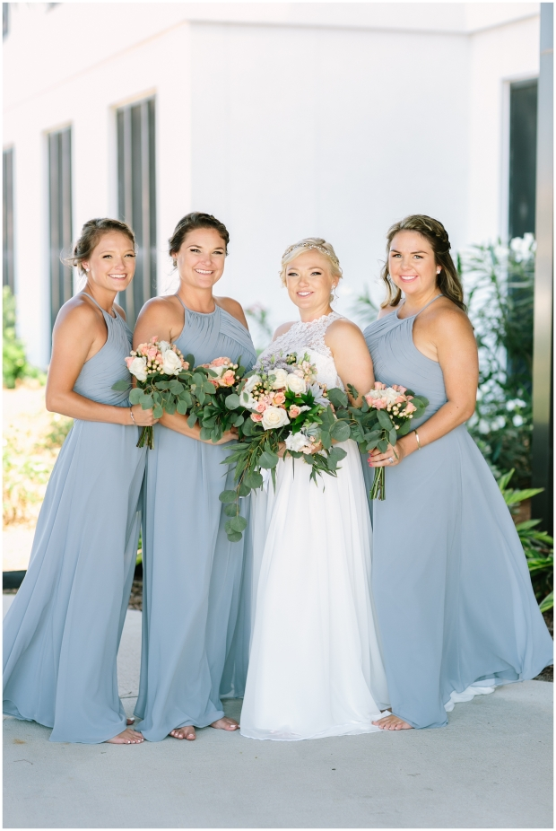 bride smiling with three bridesmaids in light blue dresses